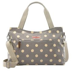 This spacious zip handbag comes with a detachable cross-body strap with an adjustable fit and four handy pockets. Brown leather trims add a stylish finish to the polka dot design. Check out the rest of the Button Spot range for matching accessories.