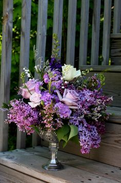 Silver dish with lavender arrangement of lilacs and roses by Simply Exquisite by the bay, LLC
