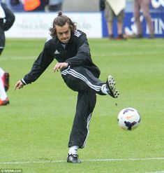 Kicking off: Harry Styles showed off his moves on the pitch as he competed in the charity ...