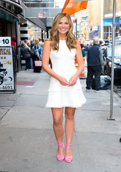 Hannah Brown is dressed in a Likely Jewel Dress and Schutz Yvi Twisted Leather Ankle-Tie Sandals.