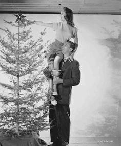 Full publicity shot of Robert Mitchum as Steve Mason holding Janet Leigh as Connie Ennis up on his shoulder as she places star atop Christmas tree.