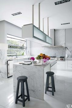In accessories designer Nancy Gonzalez's Colombia home, decorated by Jean-Louis Deniot, the kitchen features a Bulthaup hood, Wolf range, and Thassos marble floor.