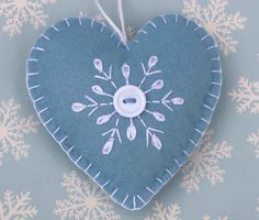 Felt heart Christmas ornament in blue with snowflake embroidery.  Blue and white Scandinavian style Christmas heart decoration. Hand embroidered snowflake design with button detail, blanket-stitched edges and a loop for hanging.  9.5cm high.  Blue background with white embroidery and button.  You can see more felt heart ornaments here; https://www.etsy.com/ie/shop/PuffinPatchwork?ref=hdr_shop_menu&section_id=19324374#policies