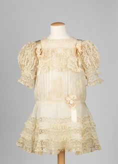 A little girl's delicate lace dress dating to circa 1908.
