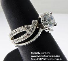 Classic and elegant! Platinum, diamond, and moissanite ring with simple platinum shadow band.  McNulty Jewelers original design