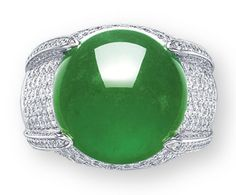 A JADEITE AND DIAMOND RING  SET WITH A CIRCULAR JADEITE CABOCHON OF BRILLIANT EMERALD GREEN COLOUR AND HIGH TRANSLUCENCY, TO THE PAVé-SET DIAMOND GALLERY AND QUARTER-HOOP, MOUNTED IN 18K WHITE GOLD, CABOCHON APPROXIMATELY 16.8 X 16.4 X 7.5 MM,