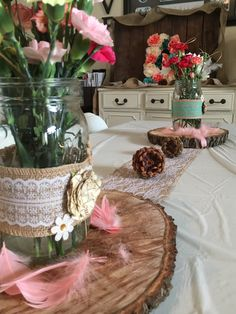 Woodsy chic, rustic themed baby shower brunch. Details include pine cones, wood slabs, feathers, Mason jars, fresh flowers, burlap runners, and coral, turquoise, gold and pink accents.