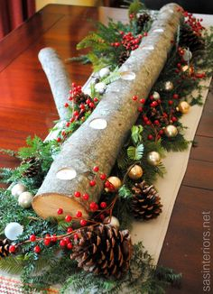 Log Centerpiece using natural greenery, berries, pinecones, and a few small ornaments .