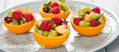 Vers fruit in sinaasappelbakje DESSERT/HAPJE – 15 MINUTEN – 4 STUKS * Leuk en gezond hapje of toetje van vers fruit met munt in een bakje van sinaasappelschil Ingrediënten 2 sinaasappels Vers fruit, zoals kiwi, appel nectarine, framboos, aardbei etc. Verse blaadjes munt, fijn gehakt 3 eetl water 1 eetl suiker