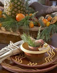 A REDWARE PLACE SETTING WITH SPRIGS OF PINE AND A CLOTH BIRD.