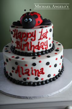 White Polka Dot Lady #13Milestones  This two tier cake is iced in white buttercream & features black and red polka dots. The borders are piped in black buttercream and the birthday message is written to cover both tiers. A gum paste lady bug tops the cake for an extra special touch.