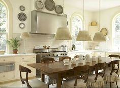 Lovely white French kitchen with long dining room table for casual entertaining in the kitchen. Love all of the big windows that bring in a lot of light.