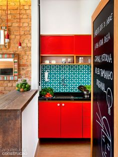 Red kitchen cabinets, turquoise square tile splashback, exposed brick, exposed light bulb with red cord, blackboard
