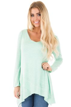 Lightly tanned smiling lemonette in minty long-sleeve chemisier with arched hem