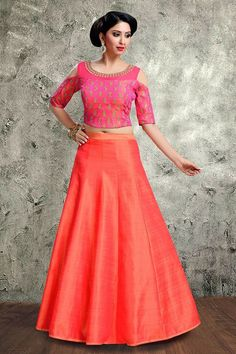 Paint this party season with this bubbly pink shot silk choli engraved with a voguish cold shoulder sleeves that is admiring its sheer net boat neckline all glammed up with floral stone work; choli elaborated with small butties finely crafted with zari thread and studded with tikkis to emphasize its excellence. The peach skirt is made up of a stiff ark silk material; tailored with sharp pleats to comprehend with the delicacy of the choli.