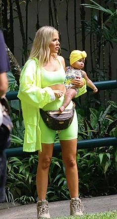 e1ea2c2c0c0 Making memories  Khloe wore a fluorescent yellow rain jacket over a neon  green bodysuit as she carried her adorable tot around a zoo to see elephants