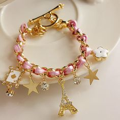 Cute Chic! ribbon charm bracelet with eiffel tower, stars, playing card motif and rhinestone charms.