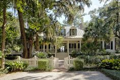 low country house, wrap around porch, tin roof, white picket fence, trees with spanish moss