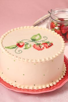 Buttercream is used to decorate a cake replicating traditional cross stitch strawberry motif.