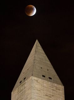 A perigee full moon, or supermoon, is seen behind the Washington Monument during a total lunar eclipse