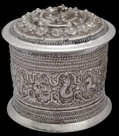 Chased Silver Betel Box Shan People, Eastern Burma 19th century height: 12.5cm diameter: 12cm, weight: 363g This chased silver betel box comprises a base and a cover. The base sits on a flared foot which is mirrored by an equally flared rim around the top of the cover. The cover stretches down over most of the box. Its sides are decorated with Burmese/Shan zodiac signs and other symbols including a fish with an elephant's head, within cartouches separated by panels filled with stylised birds…