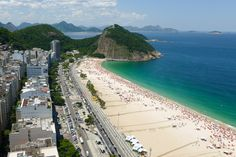 """Copacabana - Rio De Janeiro, Brazil * """"Cariocas"""" (Rio Residents) seem to live on the city's beaches: In the Copacabana neighborhood, they take to the sands for pickup volleyball and soccer games and frolicking in the waves, while the fun continues on adjacent Ipanema, a showcase for more gorgeous bodies and dental-floss swimwear.  the iconic, 124 foot statue of Christ the Redeemer with outstretched arms watches his flock from atop nearby Corcovado Mountain."""