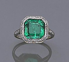 An art deco emerald and diamond ring, circa 1920 centering a cut-corner square emerald within a surround and shoulders of old single-cut diamonds; emerald weighing approximately: 3.35 carats; mounted in platinum.