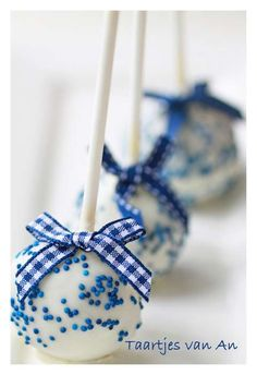 White Baby Boy Cake Pops with Blue Sprinkles and Blue Ribbon
