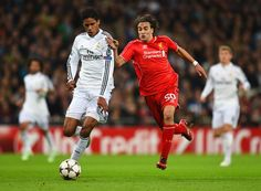 Raphael Varane Photos Photos - Raphael Varane of Real Madrid CF and Lazar Markovic of Liverpool compete for the ball during the UEFA Champions League Group B match between Real Madrid CF and Liverpool FC at Estadio Santiago Bernabeu on November 4, 2014 in Madrid, Spain. - Real Madrid CF v Liverpool FC