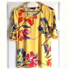 HP Dillard's Investments Tropical Floral Top Wardrobe Refresh Host Pick! Beautiful yellow floral spring/summer top by Investments, a line available at Dillard's. Features a beautiful hibiscus-like floral design in colors of red and purple among a yellow background. Keyhole front with top button and sexy vertical slit on each 3/4 sleeve. 100% polyester. Perfect condition. Great for vacation, a summer night, and more. 22 inches underarm to underarm and 26 inches shoulder to hem. Could possibly…