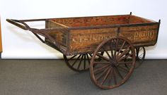 "Antique peddler's cart stenciled ""Steinberg's Inc. Radio"", 19th century; wood body, metal frame, three spoked wagon wheels with forged springs. 35""H x 72""L x 22""W."