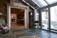 STEMNING: Peisestuen med de høye vinduene er et favorittsted i denne hytta. Innvendige vegger er en kombinasjon av tømmer og spetebordpanel, isolert med saueull i hulrommet mellom stokkene. Det er skifergulv og tregulv. Peisen er plassbygd i stein.
