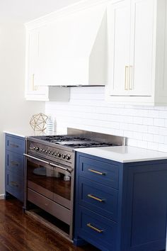 SPANISH REMODEL: KITCHEN + FAMILY ROOM | E. INTERIORS  We added a simple wood hood and this subtle subway backsplash which is timeless. The gold hardware speaks for itself!