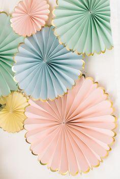 Sechs zart pastellene Papierfächer, auch Faltrosetten genannt,ergeben eine richtig schöne Dekoration an der Wand oder frei im Raum schwebend. Creme, mint, rosé und hellblau sind die unterschiedlich großen Pinwheels, allesamt haben einen goldenen Rand. Das Set beinhaltet sechs Faltrosetten in dreiGrößen: 35,5cm, 28cm und 16,5cm