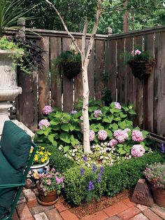 Casual Corner---Tucked against the backdrop of the fence, two hanging baskets pick up the color of the blooms in the containers and in the ground.