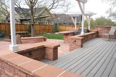 Rose sandstone walls define the formal and informal areas of this patio, while anchoring a pergola and providing lighting. By Native Edge Landscapes in Boulder, Colorado.
