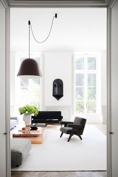 French-inspired living space with large windows, a large pendant light, and a armchair