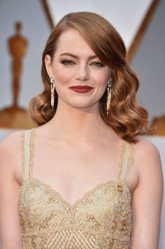 Emma Stone's glossed old Hollywood waves and matte crimson lips give a nod to Stone's winning La La Land role.