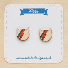 "These minimal and delicate David Bowie studs shape like cats will be perfect for a rock' n roll touch! The perfect gift for a David Bowie fan and cat lover! These tiny cat shape wooden studs are mounted on silver plated earring posts, perfect for sensitive ears! Please note that all earrings are non-refundable or exchangeable for hygiene reasons. | Dimensions | Earring: 1 cm x 1 cm – 0.4"" x 0.4"" Material: FSC birch plywood, hand painted, varnished Thickness: 3mm – 0.1"" Studs: silver plat..."
