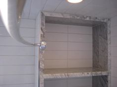 Marble shelf created from what used to be the space taken up by the broom closet. This shelf sits at one end of the tub