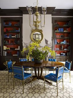 built-in bookcases + brass and blue leather chairs