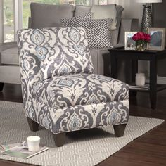 Add an elegant touch to any home with this stunning grey and blue design on a white backgound. This beautiful chair adds comfort and style to any setting.
