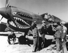 "Cleaning The Claws On The P-40E Of The Flying Tigers - The completely redesigned nose accommodating the Allison V-1710-39 engine can be seen in detail on this photo, which the author believes to show one of the AVG P-40Es. ""Flying Tigers"" received their first Es in March 1942, after the lack of spare parts and combat attrition reduced the unit's strength to only 20 flyable P-40Cs."