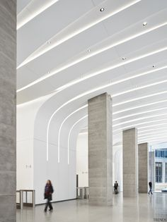 Made of tough composite Krion, the lobby wall panels in the new CME Center lobby fold over to also form the ceiling. Lighting, sprinkler systems, security and other services are all concealed within the slots between the panels. Office Building Lobby, Office Lobby, Architecture Building Design, Architecture Office, Futuristic Interior, Lobby Interior, Lobby Design, False Ceiling Design, Entry Foyer