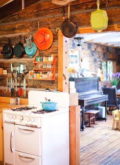 so fun, rustic and cottagey! Love the bright pots and pans and beautiful wooden walls even the living room