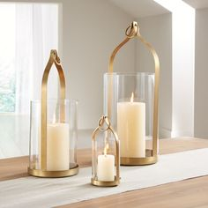 Shop Priya Brass Lanterns. Aluminum finished in matte brass with subtle antiquing shapes the graceful arabesque of these lanterns. Topped with a metal ring for hanging, each gleaming gold frame curves to a point above a glass hurricane.