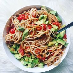 Tomato-basil spaghetti with avocado on top.Tossed chopped tomatoes and garlic into a pan with a teeny tiny bit of olive oil, seasoned with salt and pepper, and cooked it just long enough for the tomatoes to become soft. Then added a little coconut milk, marinara sauce, nutritional yeast, and fresh-chopped basil