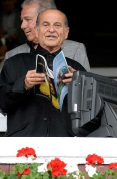 Joe Pesci looks over the odds for the first race at the Saratoga Race Course in Saratoga Springs, New York