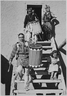 "Two Indians descending wooden stairs, carrying drums; another Indian and child near by, ""Dance, San Ildefonso Pueblo, New Mexico, 1942."" (vertical orientation) by The U.S. National Archives, via Flickr"