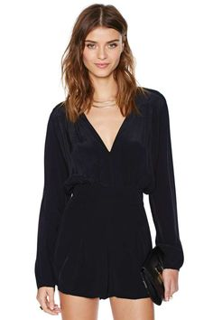 Silky black romper featuring a plunging v-neckline and pleated shorts.